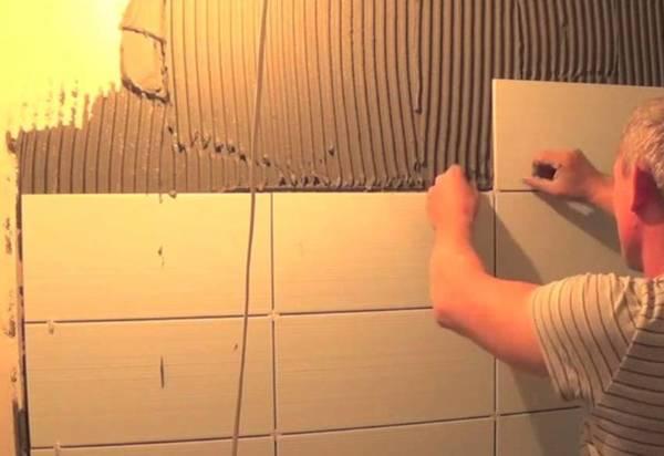 Фото как дяденька укладывает плитку на стену в ванной комнате