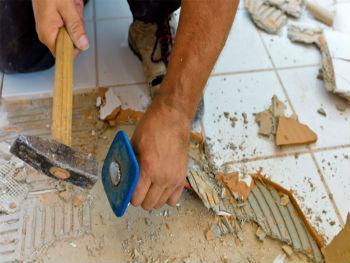 Перед тем, как выравнивать полы под плитку в ванной, нужно снять старое покрытие